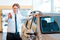 Sales man holds keys from a new car Stock Photos