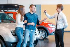 Sales consultant gives keys from new car to young couple Stock Photos