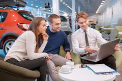 Couple communicating with the salesman in showroom Stock Photos