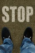 man on a tarmac road with the word Stop - stock photo