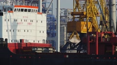 Port crane loading sand to cargo hold of the bulk carrier Stock Footage