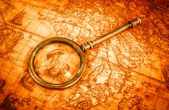 Vintage magnifying glass lies on an ancient world map - stock photo
