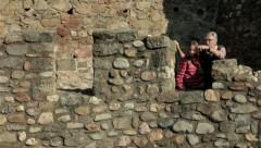 Grandfather and granddaughter tourists standing by the fence of old stone tower. Stock Footage