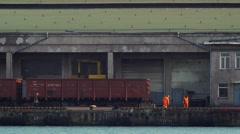 Port workers passing by railroad cars for carrying freight on pier. 4K UHD. Stock Footage