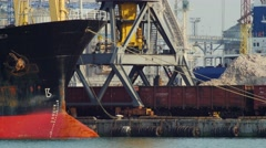 Port crane unloading sand from bulk carrier ship. Freight train and ship bow on Stock Footage