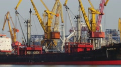 Port cranes loading bulker ship with sand Stock Footage