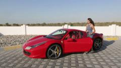 Red Ferrari 458 Spider sports car. Beautiful woman riding a car ferrari. Dubai. Stock Footage