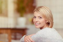Happy Woman Gripping her Arm Looking at the Camera Stock Photos