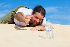 Thirsty man reaches for a bottle of water in the empty Stock Photos