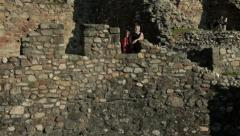 Grandfather on old tower teaching lesson from history his granddaughter, tilt up Stock Footage