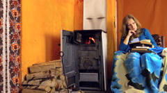 Fire flame burn in rural stove and woman read book. Zoom out Stock Footage