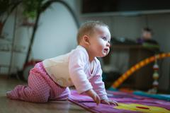 Adorable baby girl crawls on all fours floor at home. Smiling Stock Photos