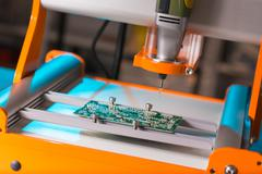 PCB Processing on CNC machine - stock photo