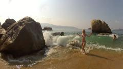 Sea wave splash on sexy girl at sand beach on background of stones Stock Footage