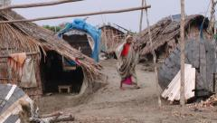 Woman walks by the street of traditional poor fishermen's village. Stock Footage