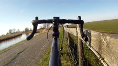 Road racer leans on fence, bicyclist passes by. Stock Footage