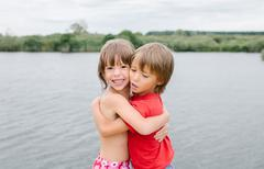 Fraternal twins hugging at the lake on hot summer day - stock photo