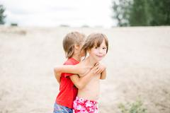 Fraternal twins hugging at the beach while playing on hot summer day - stock photo