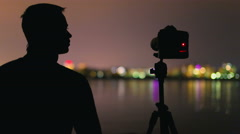 The photographer stand near the tripod with camera - stock footage
