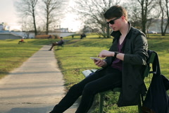 Student sitting on the bench in park and texting on smartphone Stock Footage