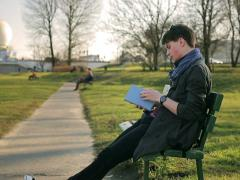 Student reading book in the park and smiling to the camera Stock Footage