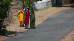 Women and children wearing traditional clothes walks along the asphalt road  Stock Footage