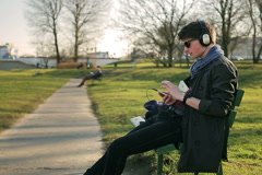 Student sitting on the bench in park and listening music on headphones Stock Footage