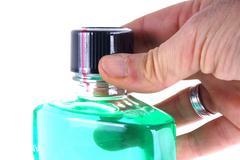 Hand holding a green mouthwash bottle on white background - stock photo