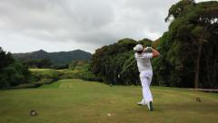 Golfer drive a ball in hawaii Stock Footage