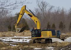 Excavator Scooping Dirt On A Jobsite - stock photo