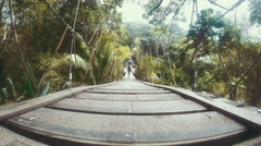 Woman crossing a wooden bridge over a jungle valley. 4K Stock Footage