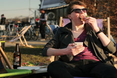 Student eating pizza in outdoor bar and using cellphone Stock Footage