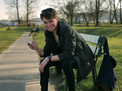 Student talking on cellphone in the park and smiling to the camera Stock Footage