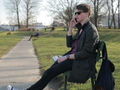 Student talking on cellphone in the park and sitting on bench Stock Footage