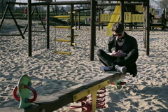 Student sitting on seesaw and texting on smartphone Stock Footage