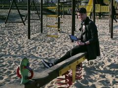 Student smiling to the camera and sitting on seesaw Stock Footage