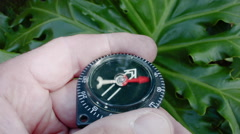 A MALE HAND HOLDS A COMPASS AS IT HITS HARD TO THE NORTH. Stock Footage