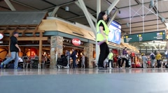 Pan shot of YVR airport terminal with people carring their luggage and prepar Stock Footage