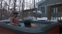 An older boy comes up out of the water of a hot tub wearing goggles and spits wh Stock Footage