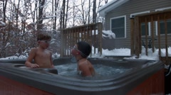 An older boy comes up out of the water of a hot tub wearing goggles and spits Stock Footage