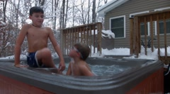An younger boy comes up out of the water of a hot tub wearing goggles and spits  Stock Footage