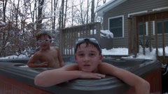 Two boys wearing goggles play together and swim in a hot tub in the backyard of  Stock Footage