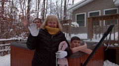 An older woman wearing a winter jacket and two young boys, in a hot tub, wave to Stock Footage