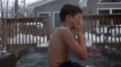 Two boys play together and swim in a hot tub in the backyard of their home Stock Footage