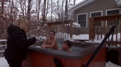 An older woman wearing a winter jacket disciples two young boys in a hot tub Stock Footage