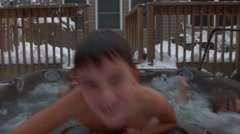 Three young boys play together and swim in a hot tub in the backyard of their ho Stock Footage