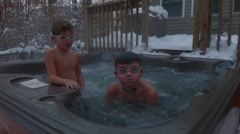 An older boy comes up out of the water of a hot tub wearing goggles and spits at Stock Footage