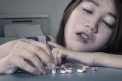 Girl using narcotic shaped pills Stock Photos