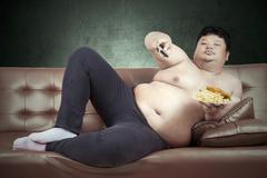 Obese man eats fast food Stock Photos