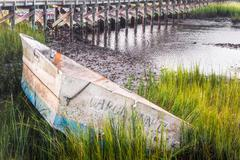 An old boat rests high on a muddy bank alongside a North Carolina harbor. Stock Photos